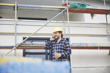 Smiling worker on the phone a construction site - MJFKF00265