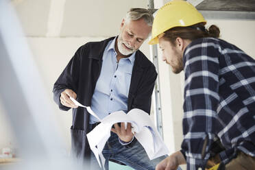 Architect and worker discussing building plan on a construction site - MJFKF00274