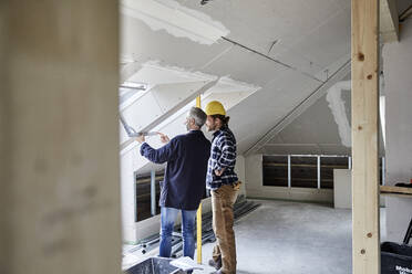 Architect and worker measuring window on a construction site - MJFKF00283