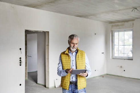 Mature man using tablet on a construction site - MJFKF00286