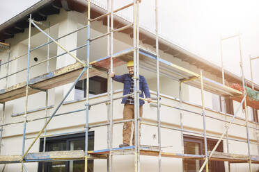 Construction worker with thumb up standing on scaffold - MJFKF00313