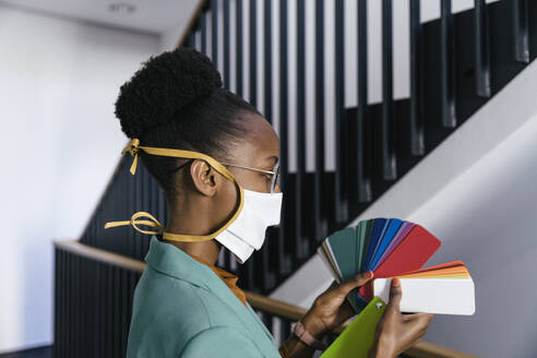 Profile of businesswoman wearing protective mask looking at color sample in staircase - MFF05765
