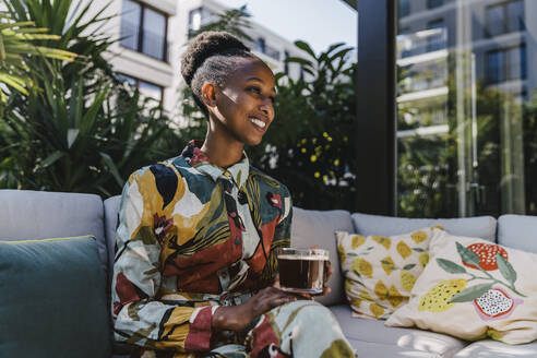 Portrait of happy young woman sitting on couch in garden drinking black coffee - MFF05795