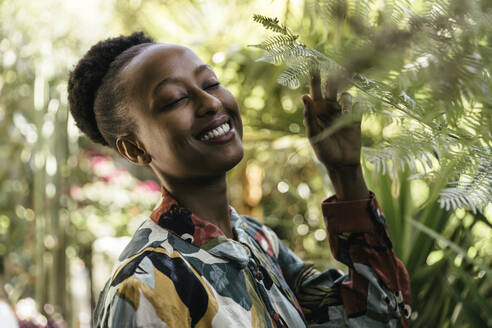 Portrait of happy young woman with eyes closed in nature - MFF05798