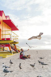 Father feeding seagulls while sitting with daughter at Miami beach, Florida, USA - GEMF03795