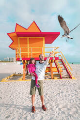 Father carrying daughter feeding seagull while standing at Miami beach, Florida, USA - GEMF03798