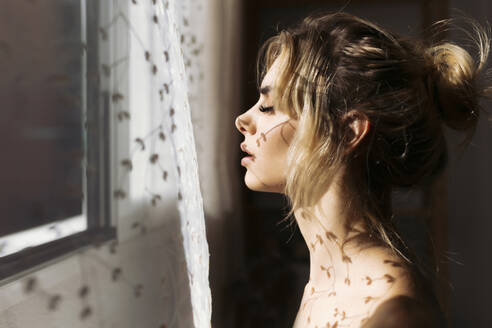 Seductive woman with shadow of curtain by window at home - TCEF00729