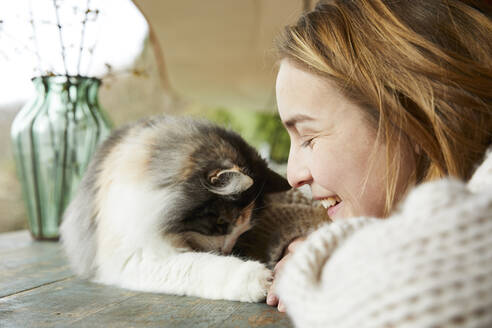 Happy woman with Norwegian forest cat on wooden table outdoors - FSF01092