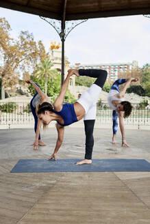 Female instructor practicing yoga with man and woman in gazebo at Ciutadella Park - JNDF00152