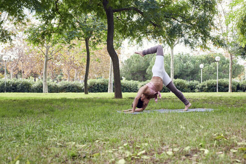 Mid adult woman practising yoga on mat in park - JNDF00155