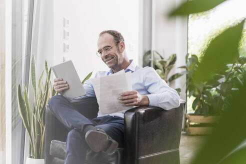 Portrait of smiling businessman with digital tablet and documents working at home - UUF20373