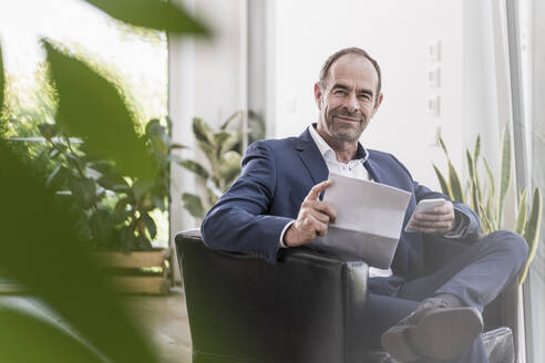 Portrait of smiling businessman with smartphone and documents working at home - UUF20376
