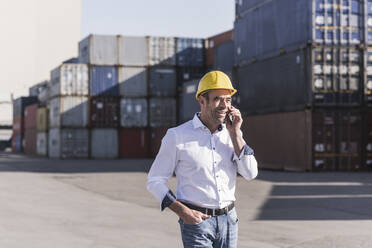 Portrait of businessman on the phone in front of cargo containers - UUF20409