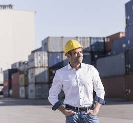 Portrait of relaxed businessman wearing safety helmet in front of cargo containers - UUF20412
