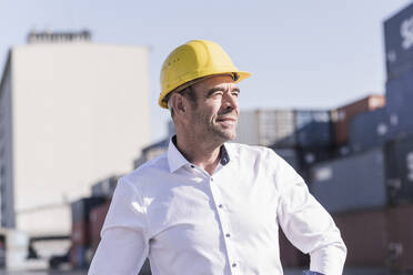 Portrait of businessman wearing safety helmet at industrial site looking at distance - UUF20415