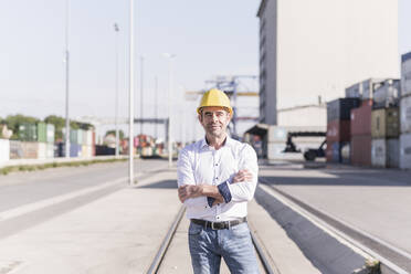 Portrait of businessman wearing safety helmet in front at industrial site - UUF20418