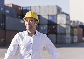 Portrait of businessman wearing safety helmet in front of cargo containers - UUF20421