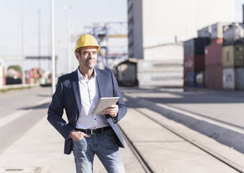 Portrait of content businessman wearing safety helmet with digital tablet at industrial site - UUF20427