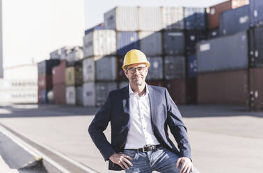 Portrait of smiling businessman wearing safety helmet at industrial site - UUF20430