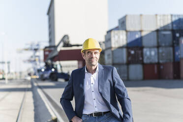 Portrait of businessman wearing safety helmet at industrial site - UUF20433
