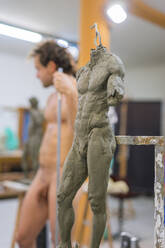 Nude model during class, focus on sculpture in foreground - FBAF01561