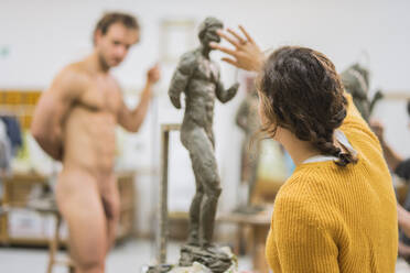 Female student forming sculpture, nude model in the background - FBAF01564