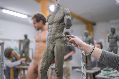 Student forming sculpture, nude model in the background - FBAF01570