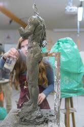 Female student spraying water on sculpture - FBAF01579