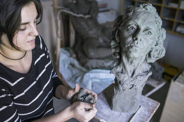 Female student forming clay for bust - FBAF01582