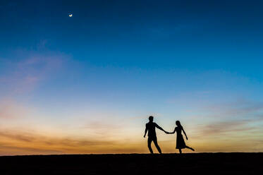 Couple at sunset in the dunes, Gran Canaria, Spain - DIGF12561