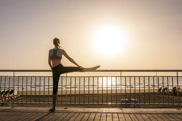 Sporty woman stretching at the seafront at sunrise, Gran Canaria, Spain - DIGF12573