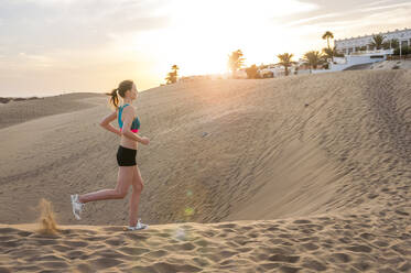 Woman running in the dunes at sunrise, Gran Canaria, Spain - DIGF12576