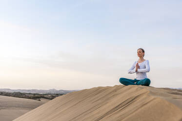 Woman practicing yoga at sunset in the dunes, Gran Canaria, Spain - DIGF12579