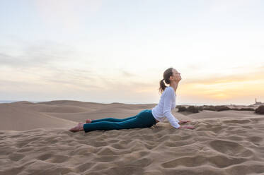 Woman practicing yoga at sunset in the dunes, Gran Canaria, Spain - DIGF12582