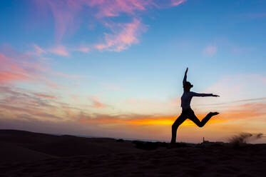 Silhouette of woman jumping at sunset in the dunes, Gran Canaria, Spain - DIGF12585