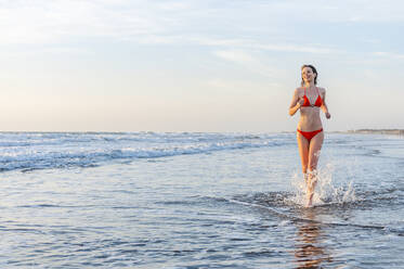 Woman wearing bikini running in the sea, Gran Canaria, Spain - DIGF12591