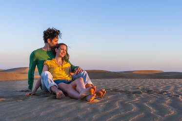 Affectionate couple sitting in the dunes at sunset, Gran Canaria, Spain - DIGF12594