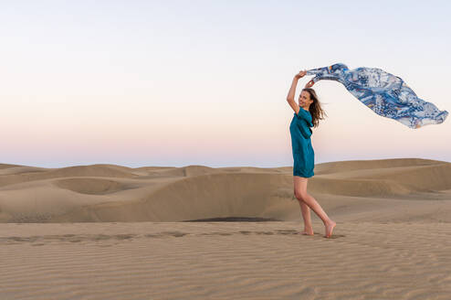 Happy woman holding cloth at sunset in the dunes, Gran Canaria, Spain - DIGF12597