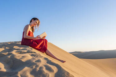 Woman in red dress sitting in the dunes using tablet, Gran Canaria, Spain - DIGF12600