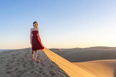 Woman in red dress walking at sunset in the dunes, Gran Canaria, Spain - DIGF12603