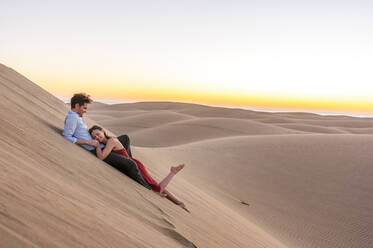 Happy couple lying in the dunes at sunset, Gran Canaria, Spain - DIGF12609