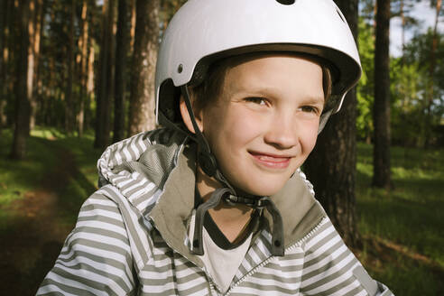 Happy boy wearing cycling helmet in forest - EYAF01078
