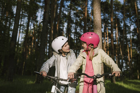 Girl and boy talking while riding bicycles in forest - EYAF01084