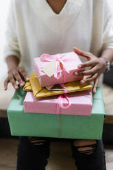 Young woman with stack of wrapped gifts - GIOF08297