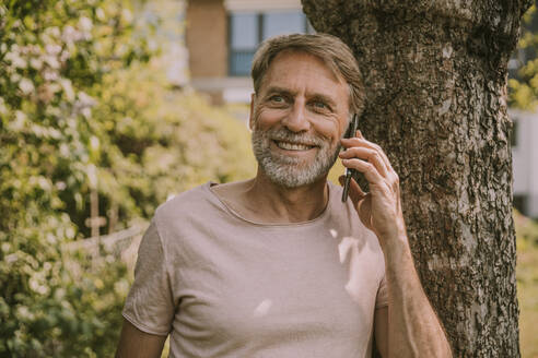 Smiling mature man looking away while talking on mobile phone against tree at garden - MFF05861