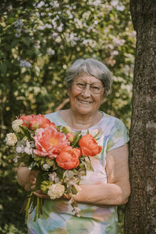Smiling elderly woman holding fresh peony bouquet by tree trunk at garden - MFF05870