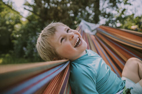 Cheerful boy relaxing on hammock at garden during sunny day - MFF05873