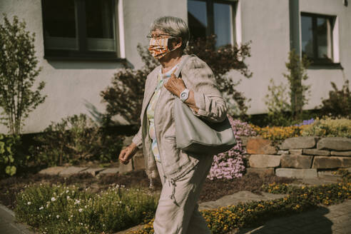 Elderly woman walking outdoors on sunny day during coronavirus - MFF05879