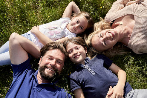 Happy family lying on grass during sunny day - AUF00523