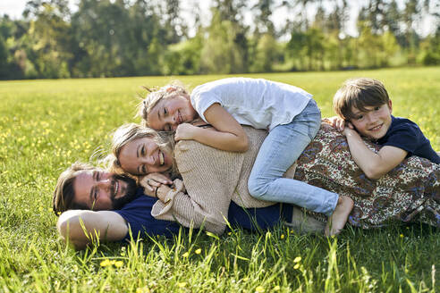 Smiling family lying on grass during sunny day - AUF00541